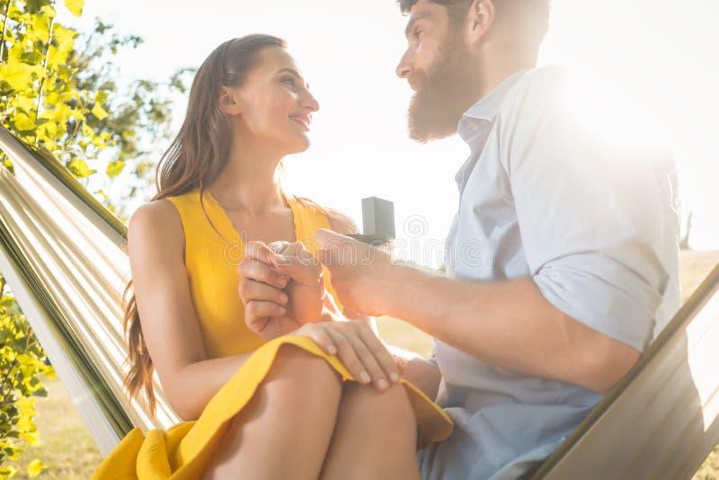 Hombre joven que hace propuesta de matrimonio a la novia hermosa mientras que imagenes de archivo
