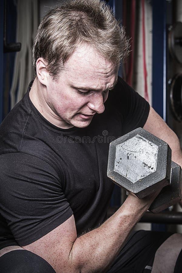 Hombre joven que hace rizos de la pesa de gimnasia en un gimnasio de Connecticut imagen de archivo
