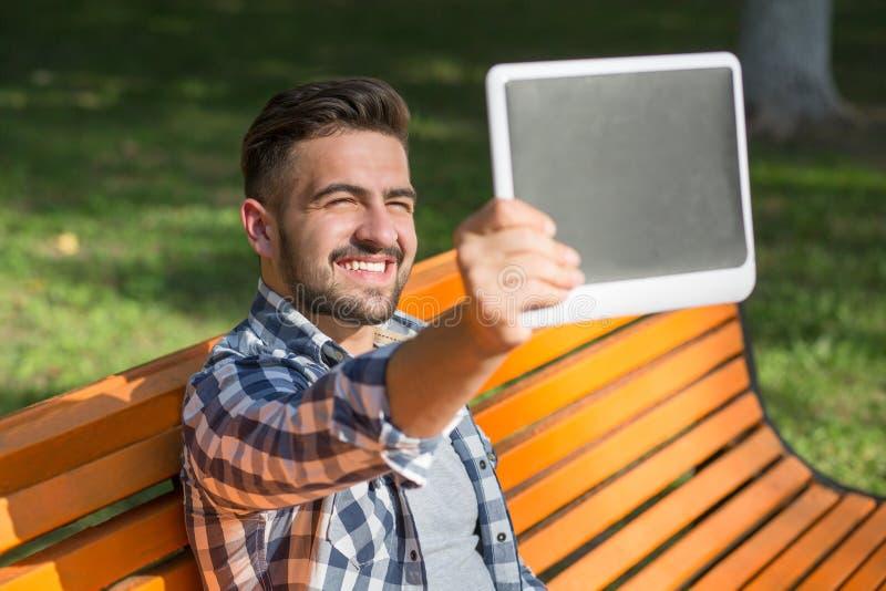 Hombre joven que hace selfies en el banco al aire libre fotos de archivo
