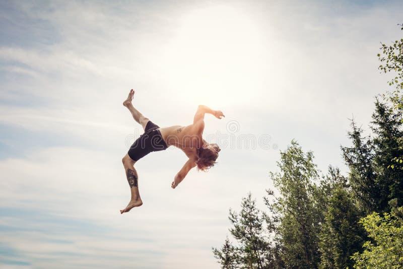Hombre joven que hace un backflip en el aire fotos de archivo libres de regalías