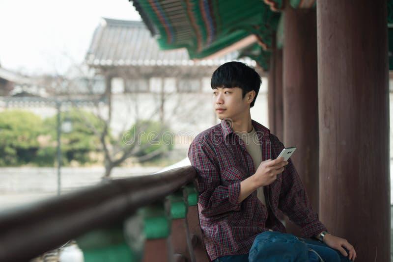 Hombre joven que hace un viaje que hace excursionismo en una casa tradicional coreana Utilice su smartphone foto de archivo