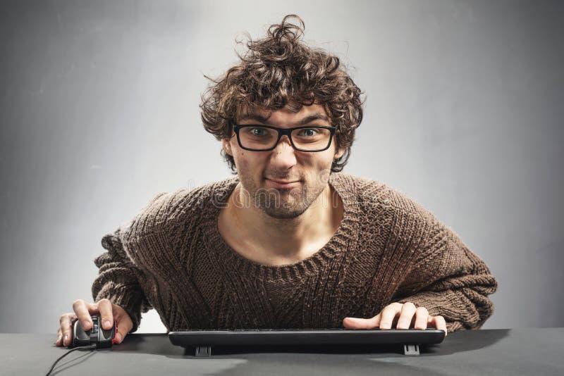 Hombre joven que juega al juego en un ordenador imagen de archivo