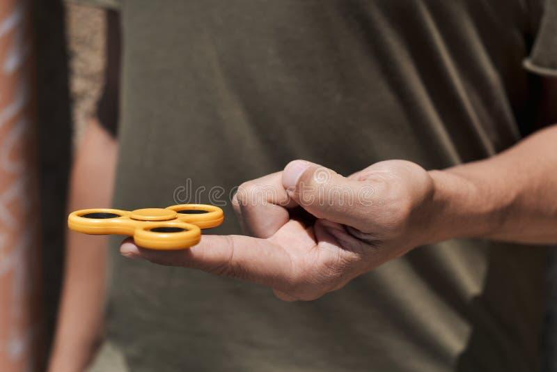 Hombre joven que juega con un hilandero de la persona agitada foto de archivo libre de regalías