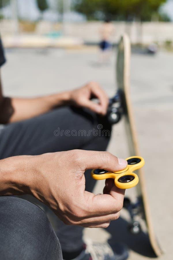 Hombre joven que juega con un hilandero de la persona agitada imágenes de archivo libres de regalías