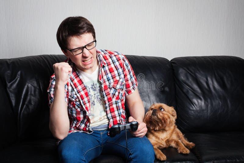 Hombre joven que juega el playthrough del juego en casa o el vídeo del recorrido El hombre atractivo está llevando las lentes Él  foto de archivo libre de regalías