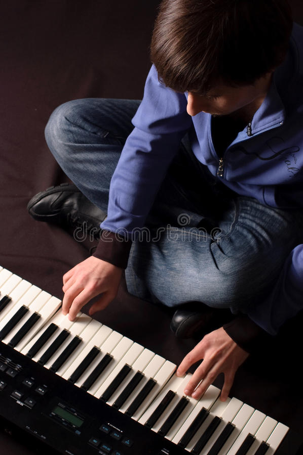 Hombre joven que juega en un sintetizador imagen de archivo
