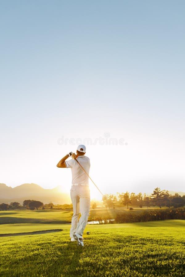 Hombre joven que juega a golf en un día soleado imagenes de archivo