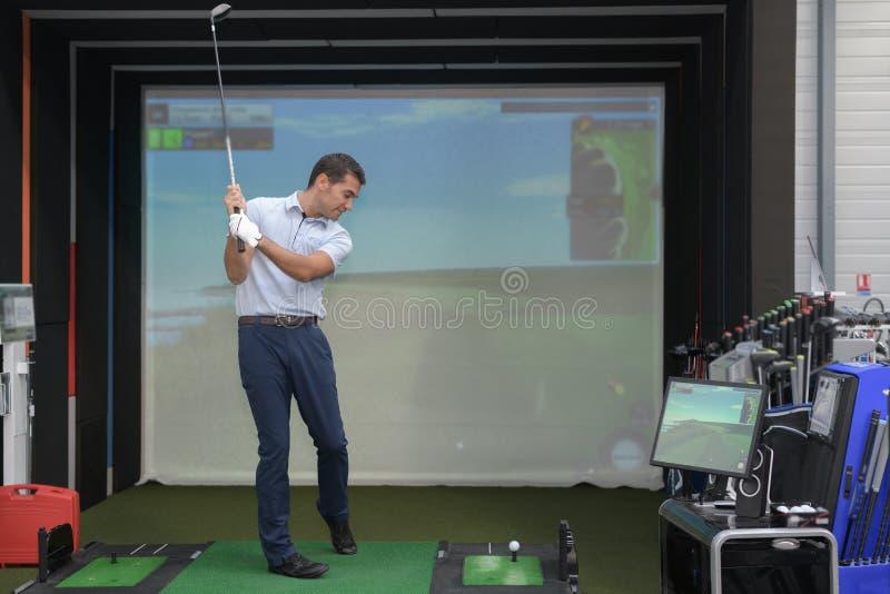 Hombre joven que juega a golf y que obra recíprocamente con el videojuego imagen de archivo libre de regalías