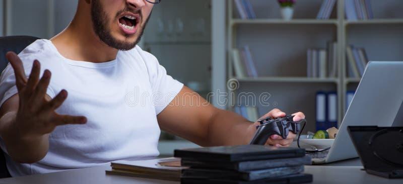 Hombre joven que juega las largases horas de los juegos atrasadas en la oficina foto de archivo libre de regalías