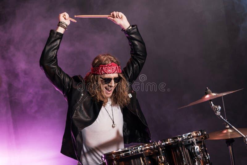 Hombre joven que juega música de heavy con los tambores fijados fotos de archivo