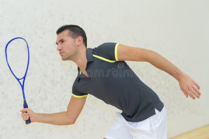 Hombre joven que juega a tenis dentro imagen de archivo libre de regalías