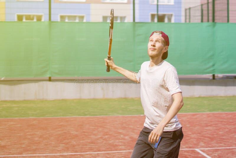 Hombre joven que juega a tenis en el tiro de fabricación al aire libre de la corte imagen de archivo