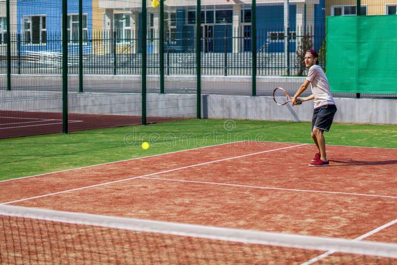 Hombre joven que juega a tenis en el tiro de fabricación al aire libre de la corte imágenes de archivo libres de regalías