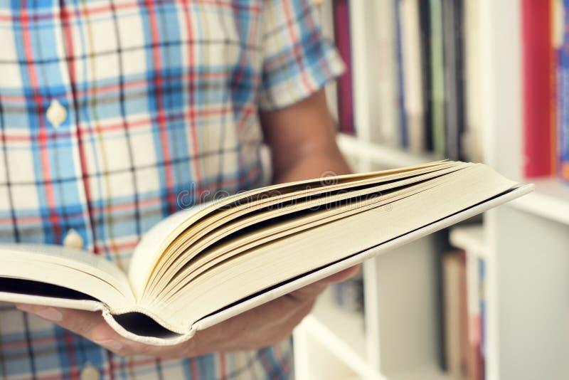 Hombre joven que lee un libro fotos de archivo