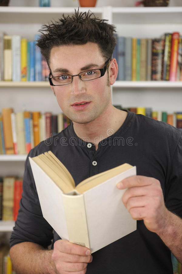 Hombre joven que lee un libro en biblioteca fotografía de archivo libre de regalías