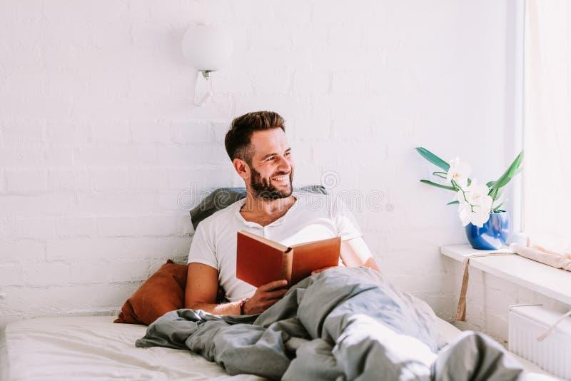 Hombre joven que lee un libro en la cama imagenes de archivo