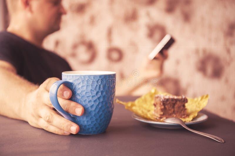 Hombre joven que lee una revista en un café En una mano a la taza de café, en el otro un dispositivo electrónico Mirada adentro a imagen de archivo libre de regalías