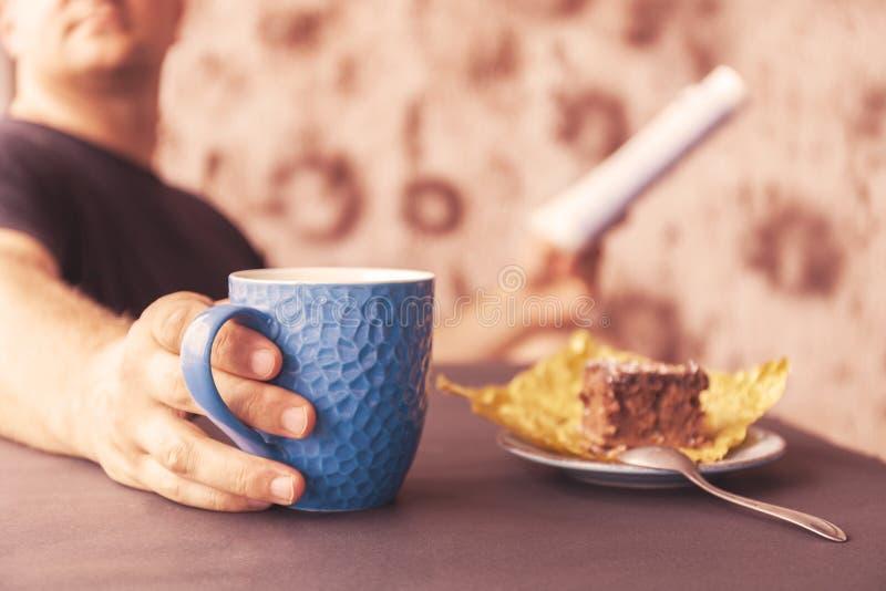 Hombre joven que lee una revista en un café En una mano a la taza de café, en el otro un periódico Mirada hacia fuera de la venta imágenes de archivo libres de regalías