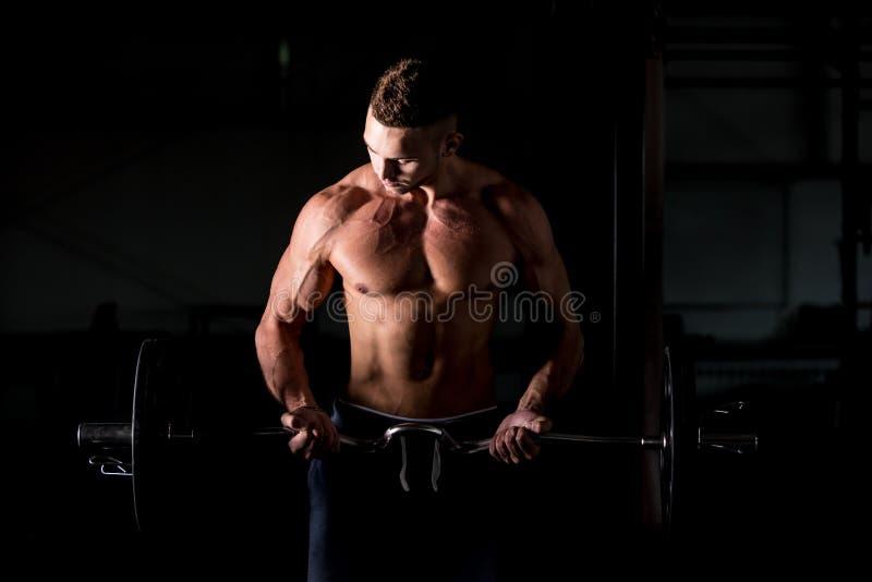 Hombre joven que levanta un barbell en gimnasio imagen de archivo