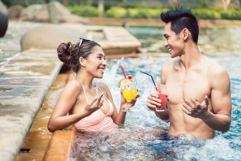 Hombre joven que liga con una mujer atractiva en una piscina de moda imagen de archivo