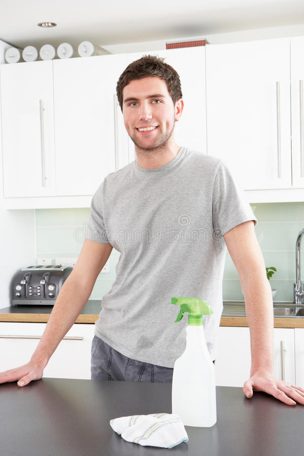 Hombre joven que limpia la cocina moderna imagen de archivo libre de regalías