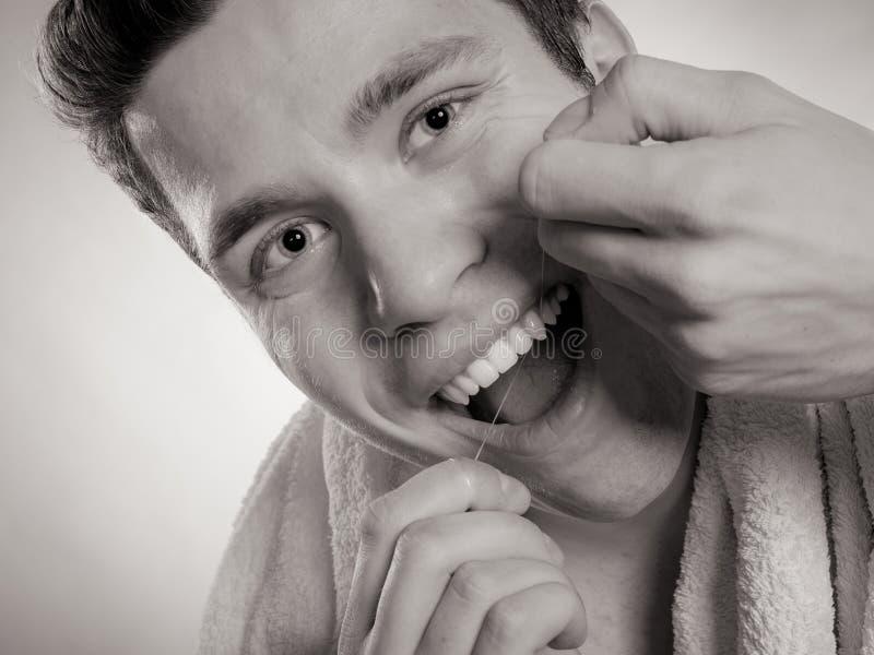 Hombre joven que limpia sus dientes blancos con seda dental foto de archivo libre de regalías