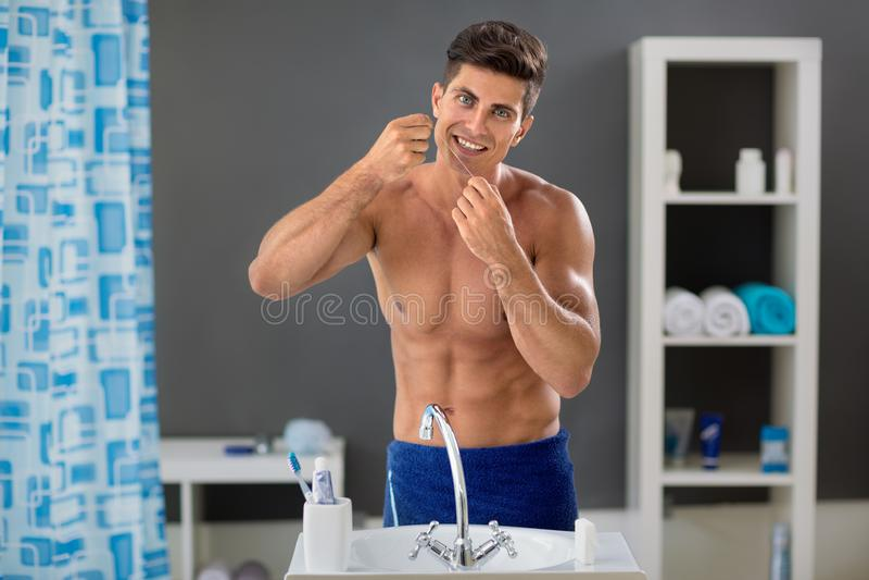 Hombre joven que limpia sus dientes con seda dental fotos de archivo libres de regalías