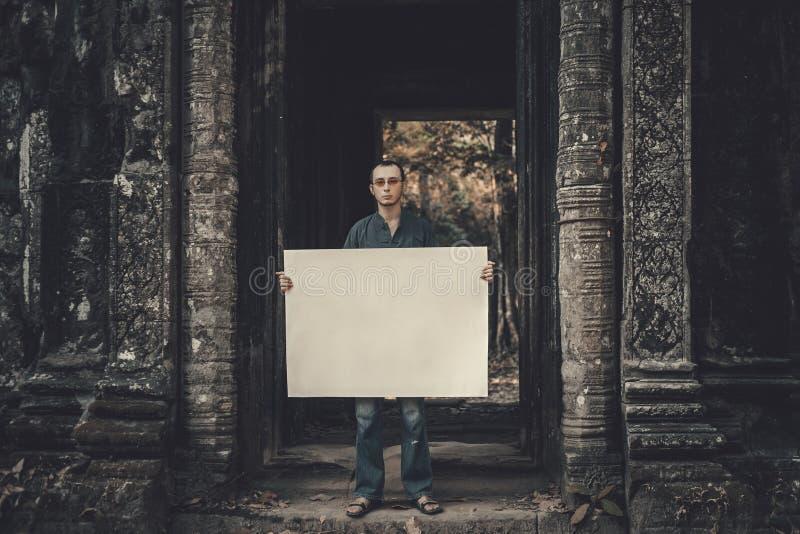 Hombre joven que lleva a cabo el cartel imagen de archivo