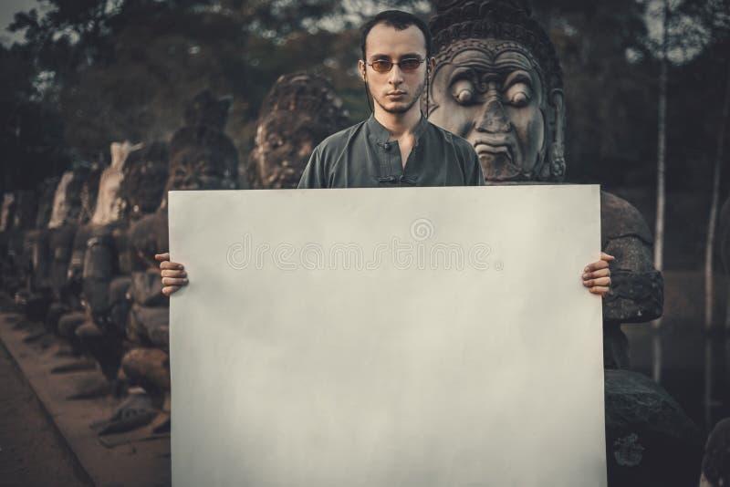 Hombre joven que lleva a cabo el cartel fotos de archivo