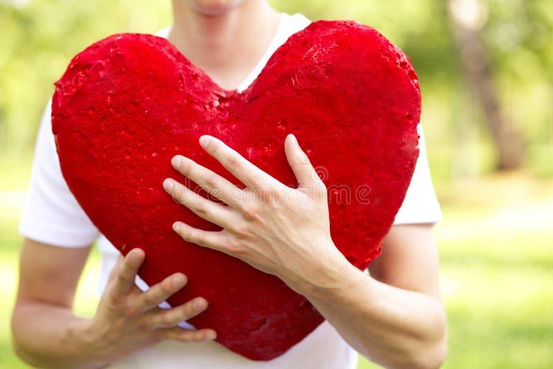 Hombre joven que lleva a cabo el corazón rojo grande fotos de archivo libres de regalías
