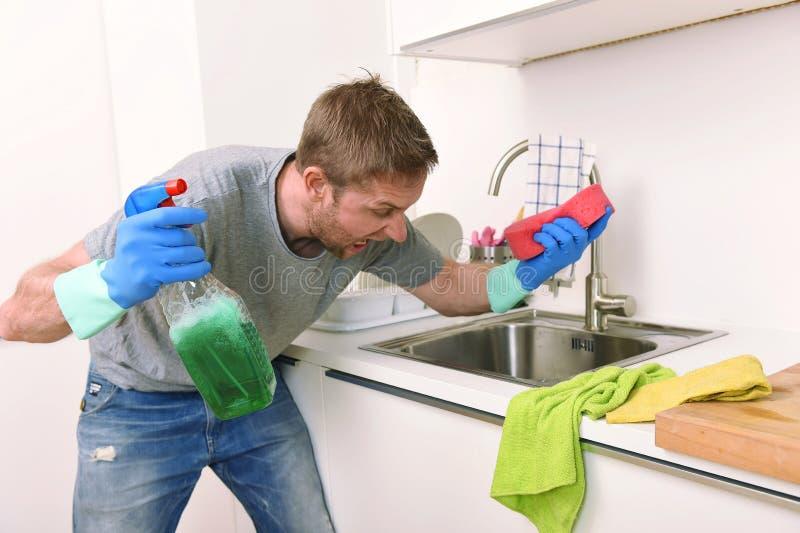 Hombre joven que lleva a cabo el espray detergente de la limpieza y esponja que lava enojado limpio de la cocina casera en la ten imagen de archivo libre de regalías