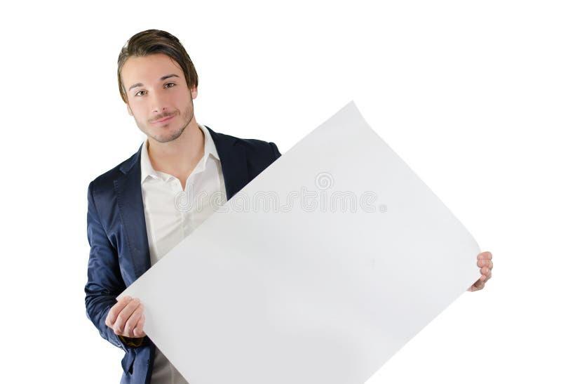 Hombre joven que lleva a cabo el tablero blanco o la muestra en blanco foto de archivo libre de regalías