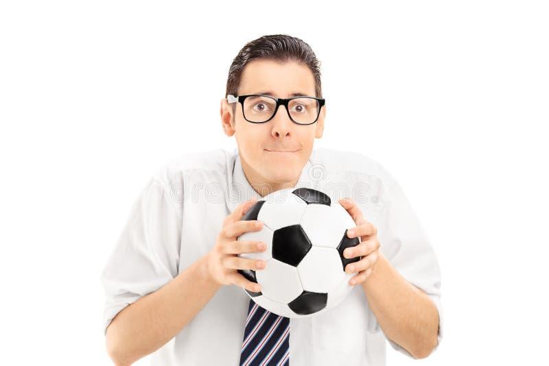 Hombre joven que lleva a cabo un fútbol y que mira el partido de deportes fotografía de archivo