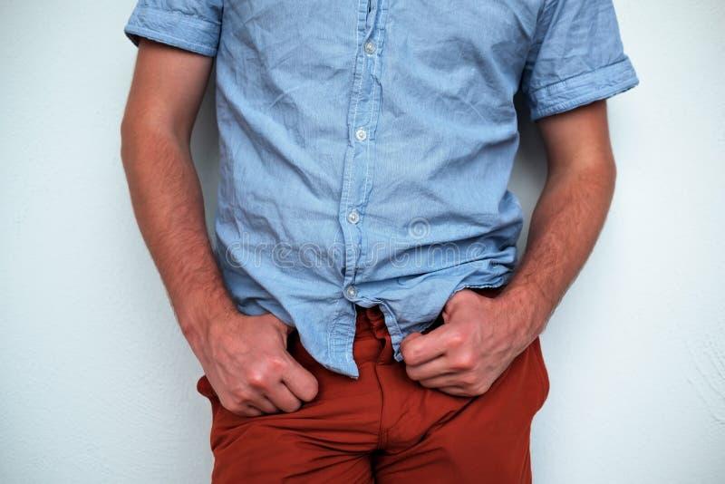 Hombre joven que lleva la camisa azul y los pantalones rojos, colocándose cerca de la pared blanca imagen de archivo libre de regalías