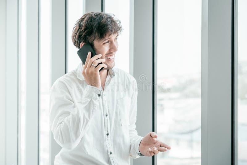 Hombre joven que lleva la ropa casual que habla en el teléfono móvil fotos de archivo