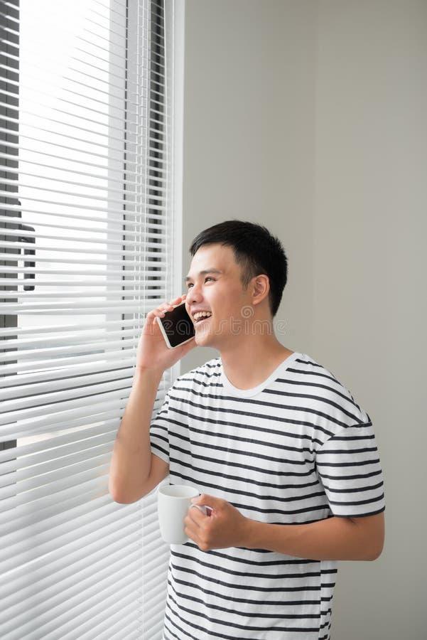 Hombre joven que lleva la ropa casual que habla en un teléfono móvil por la mañana en una ventana con el espacio de la copia foto de archivo