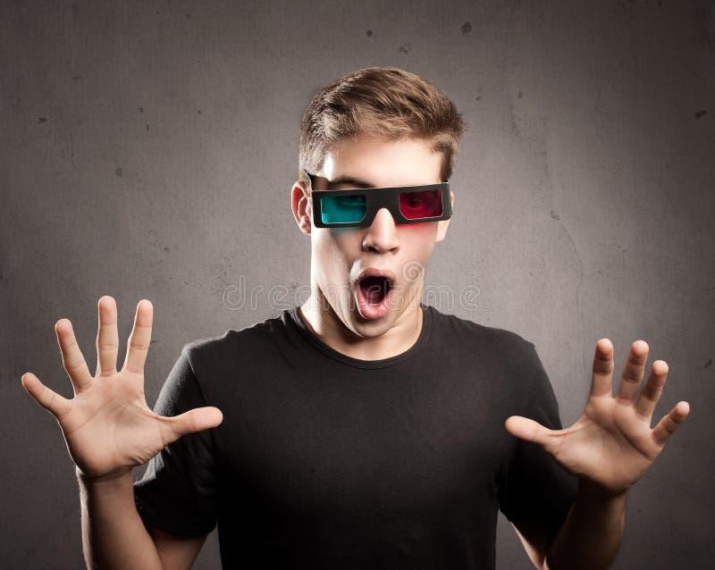 Hombre joven que lleva los vidrios 3d foto de archivo
