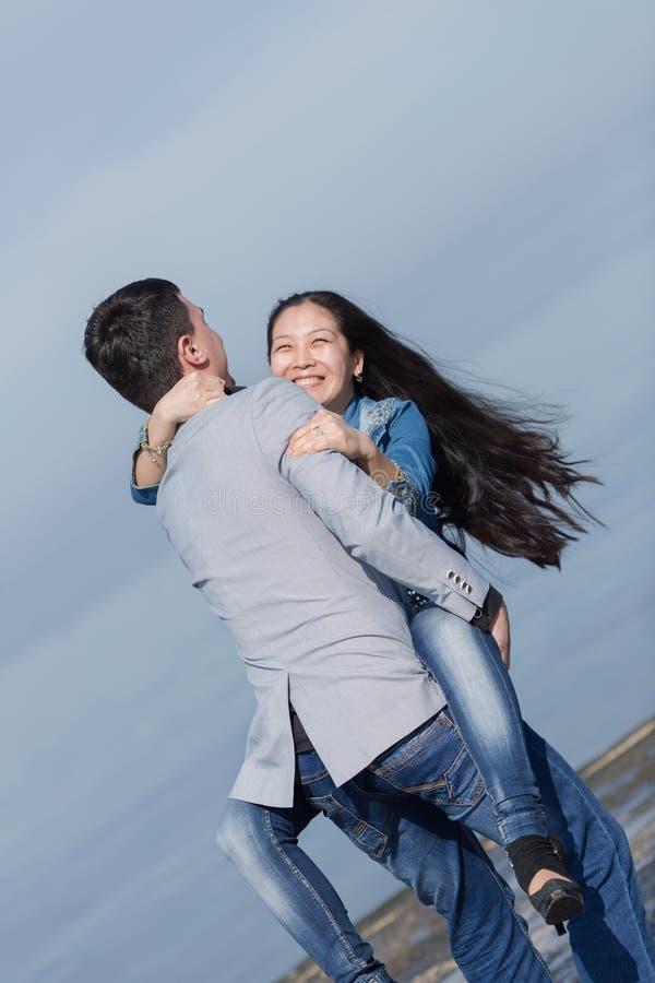 Hombre joven que lleva a su muchacha asiática foto de archivo libre de regalías