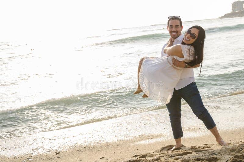 Hombre joven que lleva a su novia en sus brazos fotos de archivo