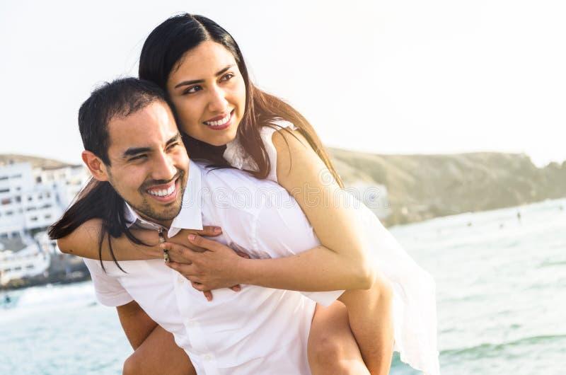 Hombre joven que lleva a su novia en sus brazos foto de archivo