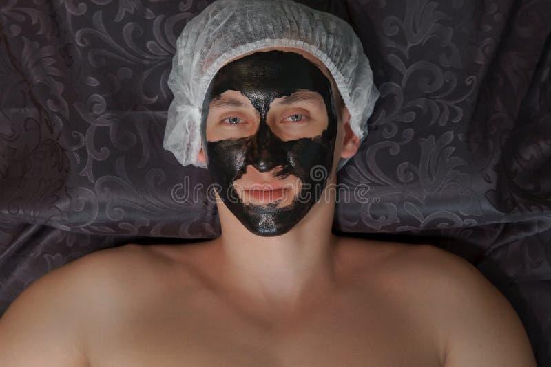 Hombre joven que lleva un procedimiento cosmético de la máscara en el balneario imagen de archivo libre de regalías