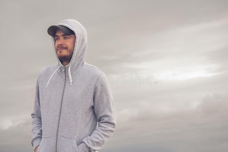 Hombre joven que lleva una sudadera con capucha y una gorra de béisbol con un día nublado foto de archivo