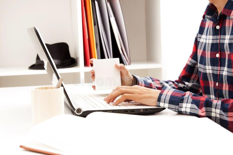 Hombre joven que mecanografía en el ordenador portátil con la bebida foto de archivo