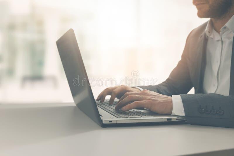 hombre joven que mecanografía en el ordenador portátil en oficina coworking moderna imagen de archivo
