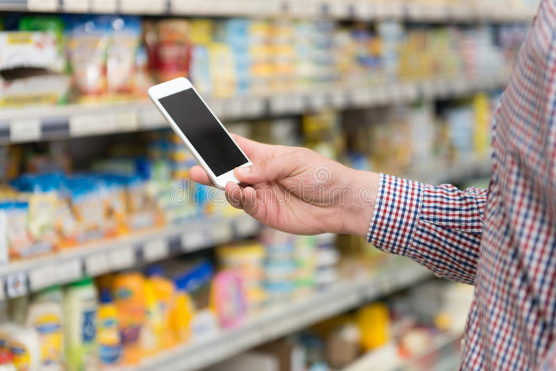 Hombre joven que mecanografía en el teléfono móvil en el supermercado fotografía de archivo