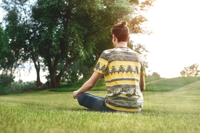 Hombre joven que medita al aire libre en el parque, sentándose con los ojos cerrados y sus manos juntos disfrutar de la naturalez fotos de archivo libres de regalías