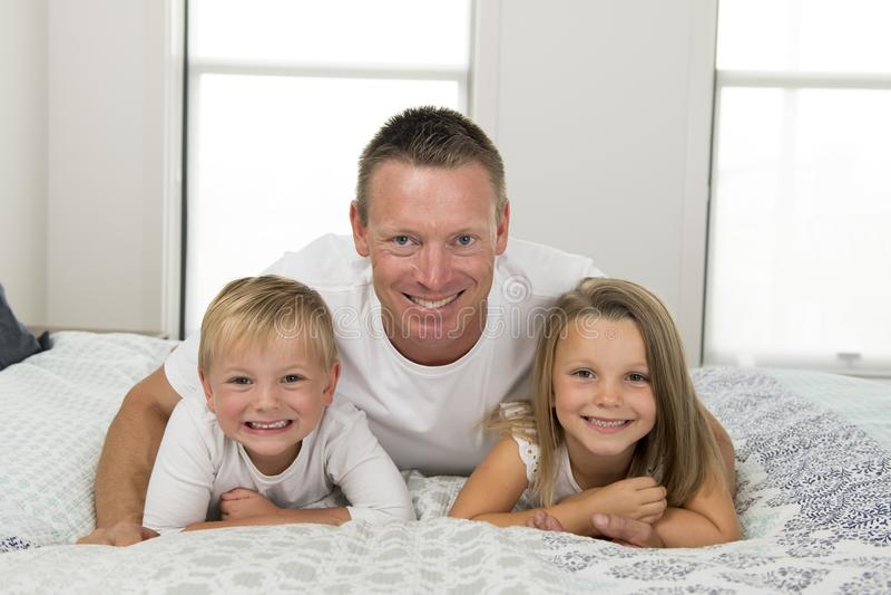 Hombre joven que miente en cama así como sus pequeños el jugar del hijo del dulce 3 y 7 años y de la hija feliz en los niños l de imagen de archivo