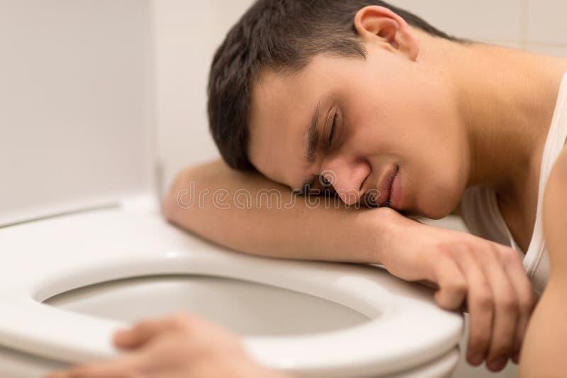 Hombre joven que miente en el asiento de inodoro. fotografía de archivo libre de regalías