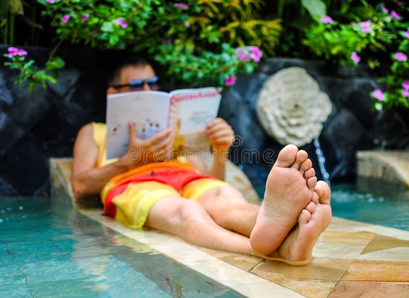 Hombre joven que miente en piscina y revista de la lectura fotos de archivo libres de regalías