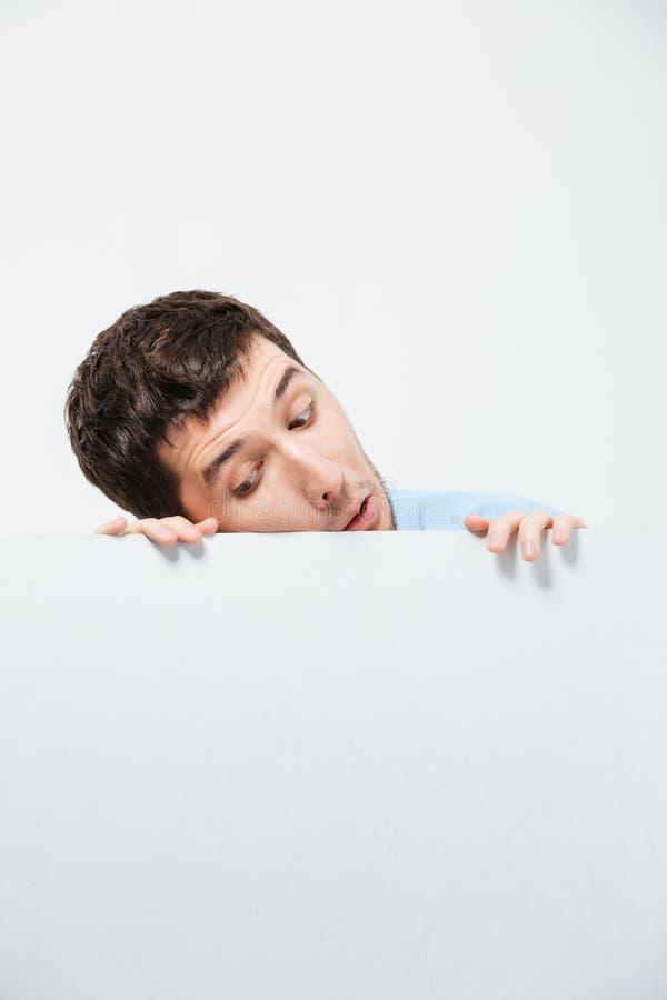 Hombre joven que mira a escondidas de tablero en blanco fotografía de archivo